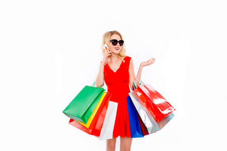 Young woman shopaholic with color paperbags talking on phone