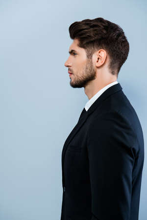 businessman suit: Side view of confident serious man in black suit Stock Photo