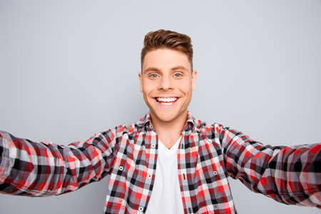 beaming: Happy young guy with beaming smile making selfie