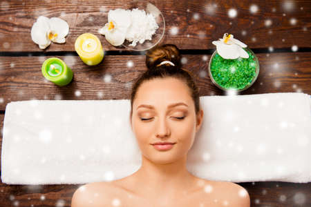 Top view of cute young woman laying in spa salon with closed eyes, xmas concept