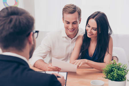 Successful lawyer giving consultation to family couple about buying house Фото со стока