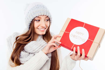 Cheerful woman  in warm hat and scarf holding package and congratulate with xmas