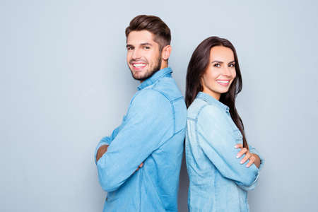 Cheerful hsppy man and woman with crossed hands standing back to back