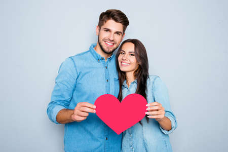 Young happy couple in love holding red paper heart