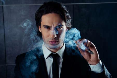 macho: Portrait of brutal macho man holding cigar with smoke Stock Photo