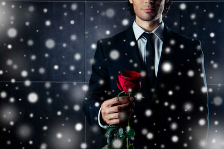 formalwear: Closeup photo of  man in formalwear  holding red rose on snowy Christmas background