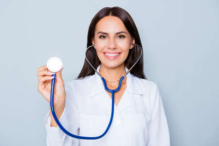 healthcare worker: Beautiful female healthcare worker with stethoscope on blue background Stock Photo