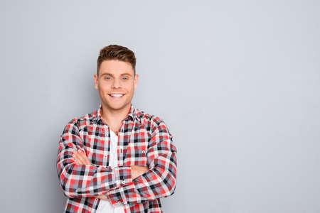 灰色の背景に交差させた手で幸せな陽気な若い男 写真素材