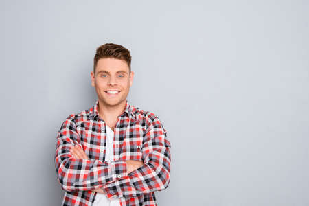 Happy cheerful young guy with crossed hands on gray background
