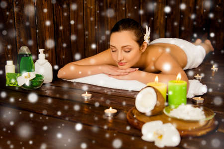 Calm pretty young woman laying in spa salon, new year concept Stock Photo