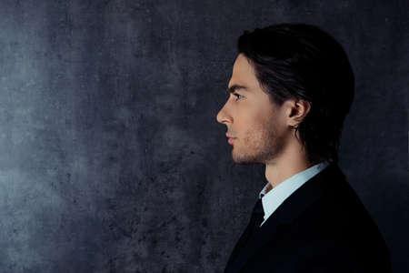 formalwear: Side-view photo of harsh young man in formalwear