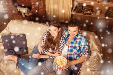 pareja viendo television: Attractive couple watching tv with popcorn on xmas night