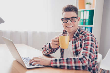 Happy smiling man in glasses drinking coffee while typing on laptop