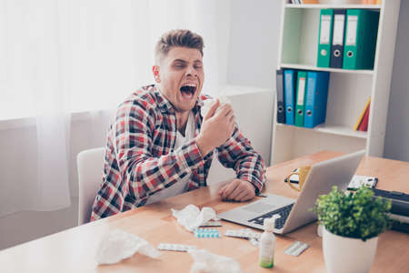 rheum: Young businessman with grippe working on laptop and sneezing in napkin
