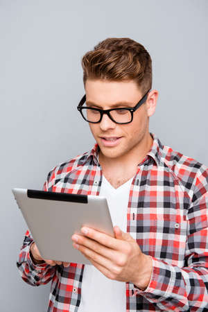 read news: Handsome man in glasses using digital tablet to read news