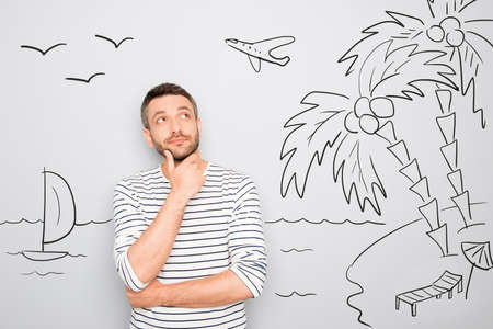 minded: cheerful minded man dreaming about vacation and looking at drawing on wall Stock Photo