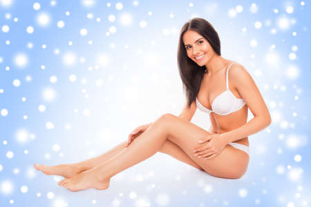 Happy woman in lingerie  touching her smooth legs covered with snowflakes Stock Photo