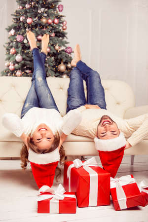 Two lovers in santa hats lying on sofa with raised up legs