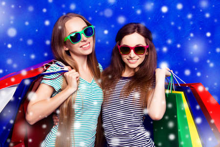paperbags: Two beautiful women in glasses with colorful paperbags on snowy winter background Stock Photo