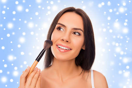 makeups: Beautiful  woman applying powder with makeups brush before xmas party Stock Photo