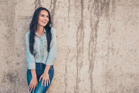 beaming: Beautiful woman with beaming smile posing near stone wall