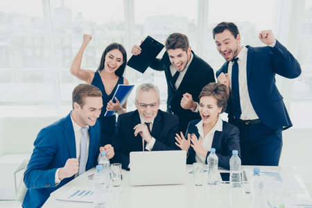 triumphing: Great news! Happy smiling businesspeople triumphing with raised fists Stock Photo