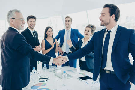 resolving: Happy businessmen shaking hands for successful resolving dispute Stock Photo