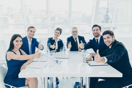 famous people: Briefing. Group of famous successful business people showing thumbs up