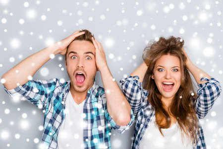 Surprised man and woman screaming and touching hair on snowy background Stock Photo