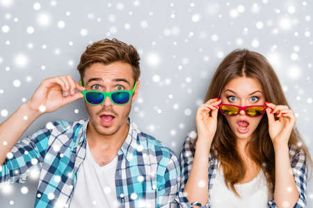 Surprised man and woman in glasses with open mouth on the background of snowfall