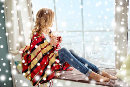 Young woman in plaid with cup of hot tea basking on xmas holidays