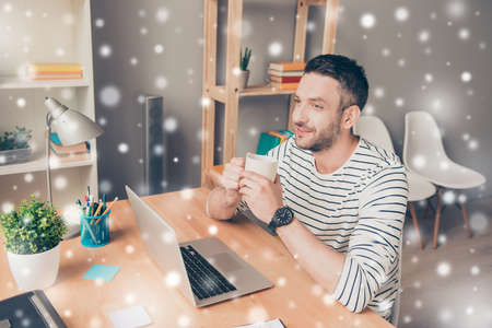 Happy man drinking coffee and dreaming on winter background