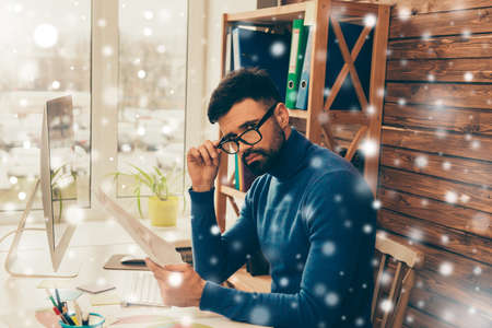 businessman pondering documents: Serious businessman in glasses doing paperwork on snowy background Stock Photo