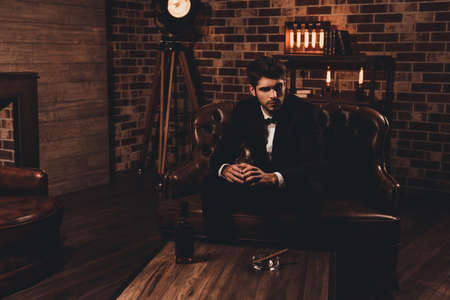 Elegant man in black suit with glass of brendy sitting in luxury room