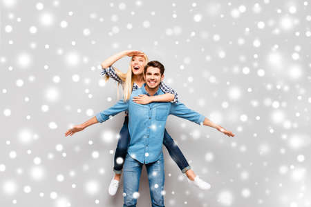 Happy man carrying his smiling girlfriend on the back on winter background Stock Photo