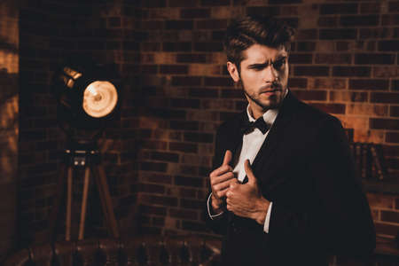 Portrait of sexy macho man wearing black tuxedo and bow-tie in loft Stock Photo