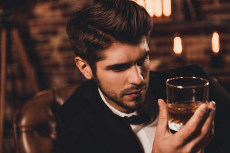 Portrait of rich handsome man holding glass of cognac and relaxing