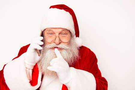 shh: Portrait of happy Santa Claus talking on phone and showing shh gesture
