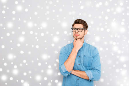 Handsome ponder young businessman in glasses on snowy winter background