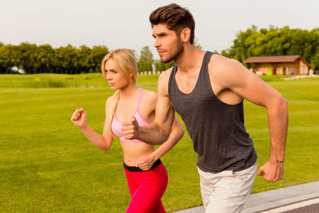 keeping fit: Healthy man and woman keeping fit and running in the park Stock Photo