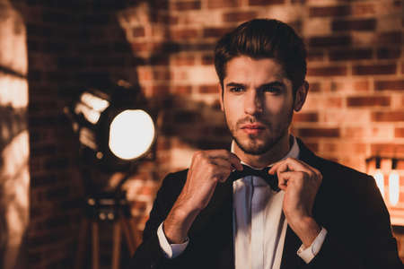 Portait of confident handsome man corecting his bow tie and wearing for event party Stock Photo