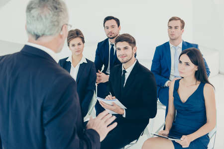 couching: Group of happy colleagues listening to report of their boss