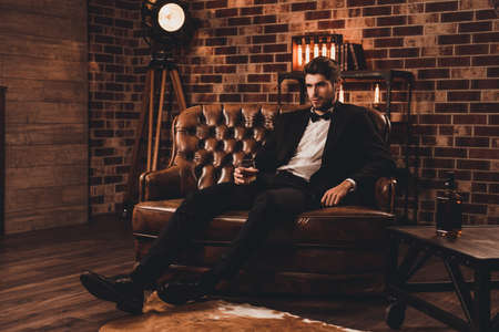 Young man in suit resting on sofa with glass of brendy after working day Archivio Fotografico