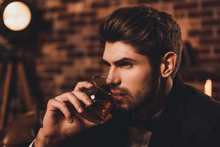 Portrait of sexy young handsome man drinking cognac