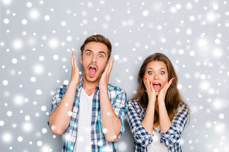 Portrait of shocked man and woman screaming on snowy winter background