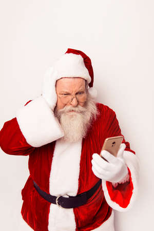 Confused Santa Claus wearing red costume reading messege on phone  while standing white background Stock Photo