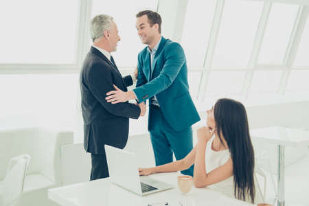 Two happy businessmen shaking hands after meeting