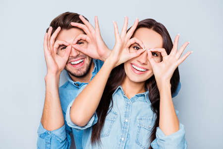 쾌활한 행복한 커플을 사랑하고 눈을 가까이에 손가락을 들고 스톡 콘텐츠
