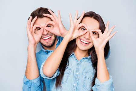 poblíž: Veselý šťastný pár v lásce baví a drží prsty u očí Reklamní fotografie
