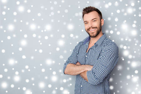 Portrait of happy handsome bearded man with crossed hands on winter background Stock Photo